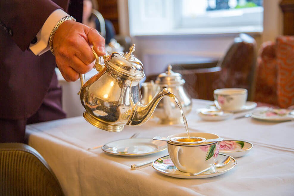 Tea being poured in elegant surroundings. An example of Afternoon Tea etiquette.